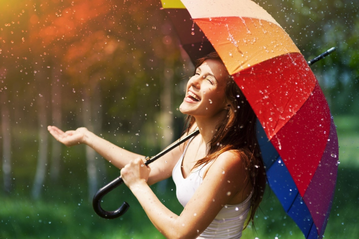 Happy-Girl-With-Rainbow-Umbrella-Under-Summer-Rain-wide-i